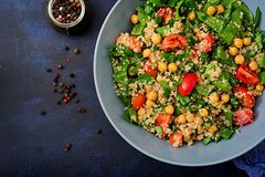 Dietary menu. Healthy vegan salad of fresh vegetables. Tomatoes, chickpeas, spinach and quinoa in a bowl Royalty Free Stock Photos