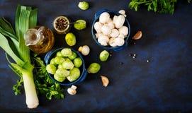 Dietary menu. Ingredients: Vegetables - Brussels sprouts, mushrooms, leeks and herbs on a dark background. Royalty Free Stock Image