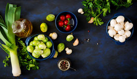Dietary menu. Ingredients: Vegetables - Brussels sprouts, mushrooms, leeks and herbs on a dark background. Top view. Vegetables menu royalty free stock photo