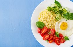 Dietary menu. Millet porridge and tomato, cucumber salad and fried eggs. Healthy breakfast. Dietary menu. Millet porridge and tomato, cucumber salad and fried stock image