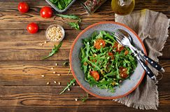 Dietary menu. Vegan cuisine. Healthy salad with arugula, tomatoes and pine nuts. Flat lay. Top view royalty free stock photo
