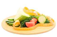Dietary mixed vegetables. Assorted vegetables cabbage, greens, zucchini and tomatoes on a cutting board with a measuring tape stock photos