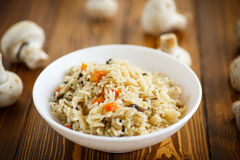 Dietary pilaf with mushrooms. On a wooden table Stock Photo