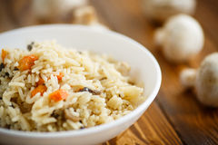 Dietary pilaf with mushrooms. On a wooden table Royalty Free Stock Images