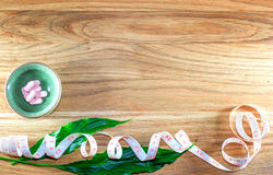 Dietary pills vie centimeter on wooden background. Stock Photos