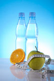 Dietary products. Fruits with measure tape and mineral water Stock Photography