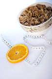 Dietary products. Cornflakes and slice of orange with measure tape Royalty Free Stock Photos
