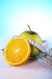 Dietary products. Green apple and slice of orange with measure tape Royalty Free Stock Photo