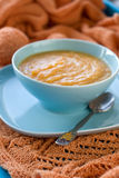 Dietary pumpkin porridge in the blue plate on an orange knitted Stock Image