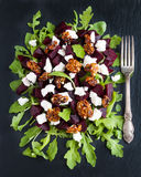 Dietary salad of beets, arugula, feta cheese and caramelized walnuts with olive oil and lemon juice. Black stone background, top v Royalty Free Stock Photo