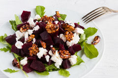 Dietary salad of beets, arugula, feta cheese and caramelized walnuts with olive oil and lemon juice. White wooden table Stock Photos