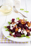 Dietary salad of beets, arugula, feta cheese and caramelized walnuts with olive oil and lemon juice. White wooden table Royalty Free Stock Images