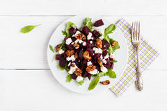 Dietary salad of beets, arugula, feta cheese and caramelized walnuts with olive oil and lemon juice. White wooden table, top view Stock Images