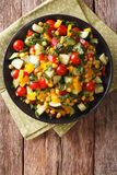 Dietary salad of corn, tomatoes, cucumbers and pepper. vertical. Dietary salad of corn, greens, tomatoes, cucumbers and pepper close-up on the table. vertical Stock Images