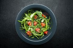 Dietary salad with mixed herbs and vegetables in a bowl on a black background royalty free stock photos