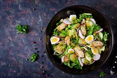 Dietary salad with mussels, quail eggs, cucumbers, radish and lettuce. Healthy food. Seafood salad. Top view. Flat lay Stock Photo