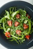 Dietary salad in a plate of arugula, paprika and tomatoes. Healthy eating.  royalty free stock photos