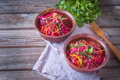 Dietary salad with sea kale, carrots, beets and sesame, sprinkled with olive oil in rustic ceramic bowl on wooden background. Detox concept stock photos