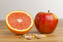 Dietary supplement vs fruits Stock Images