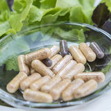 A dietary supplements Capsules on glass dish with Fresh vegetabl Stock Photos