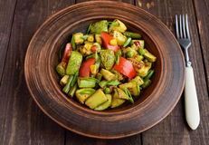 Dietary vegetarian salad with grilled zucchini, fresh tomatoes, sweet corn and herbs in a clay bowl on dark wooden background Stock Image