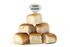 Dietary warning or gluten/wheat allergy warning. (Fresh bread rolls with Tasty Gluten text tag on white background Stock Photography