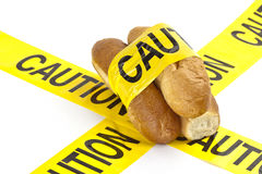 Dietary warning or gluten/wheat allergy warning. (Fresh French bread wrapped in yellow caution tape Stock Photos