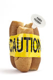Dietary warning or gluten/wheat allergy warning. (Fresh French bread wrapped in yellow caution tape Stock Photo