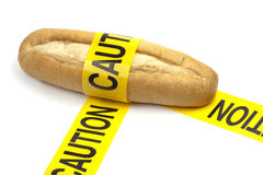 Dietary warning or gluten/wheat allergy warning. (Loaf of bread wrapped in yellow caution tape Stock Photos