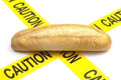 Dietary warning or gluten/wheat allergy warning. (Loaf of bread with yellow caution tape Stock Photo
