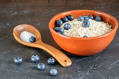 Dietetic aotmeal flakes with blueberries. Dietetic aotmeal flakes with blueberries in the bowl a on the black background stock photo