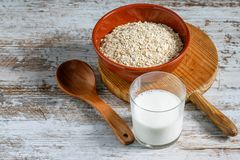 Dietetic aotmeal flakes with milk . Dietetic aotmeal flakes in the bowl and a glass of milk on the white background stock image