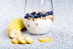 Dietetic breakfast - yoghurt with mueasli and huckleberries and banana.  royalty free stock photos