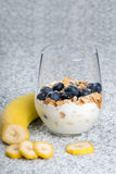 Dietetic breakfast - yoghurt with mueasli and huckleberries and banana.  royalty free stock images