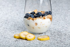 Dietetic breakfast - yoghurt with mueasli and huckleberries and banana.  Royalty Free Stock Photography