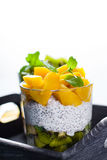 Dietetic dessert. Dietetic dessert in the form of a fresh fruit salad with kiwi and peach with chia seeds and yoghurt served in a glass royalty free stock images