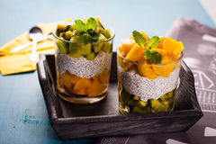 Dietetic dessert. Dietetic dessert in the form of a fresh fruit salad with kiwi and peach with chia seeds and yoghurt served in a glass royalty free stock photos