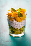 Dietetic dessert. Dietetic dessert in the form of a fresh fruit salad with kiwi and peach with chia seeds and yoghurt served in a glass royalty free stock photo
