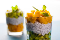 Dietetic dessert. Dietetic dessert in the form of a fresh fruit salad with kiwi and peach with chia seeds and yoghurt served in a glass stock photos