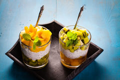 Dietetic dessert. Dietetic dessert in the form of a fresh fruit salad with kiwi and peach with chia seeds and yoghurt served in a glass stock images