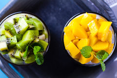 Dietetic dessert. Dietetic dessert in the form of a fresh fruit salad with kiwi and peach with chia seeds and yoghurt served in a glass.Looking at the scene stock photography
