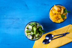 Dietetic dessert. Dietetic dessert in the form of a fresh fruit salad with kiwi and peach with chia seeds and yoghurt served in a glass.Looking at the scene stock image