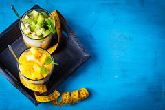 Dietetic dessert. Dietetic dessert in the form of a fresh fruit salad with kiwi and peach with chia seeds and yoghurt served in a glass and lying tailor tape royalty free stock images