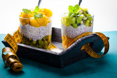 Dietetic dessert. Dietetic dessert in the form of a fresh fruit salad with kiwi and peach with chia seeds and yoghurt served in a glass and lying tailor tape stock photography