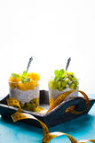 Dietetic dessert. Dietetic dessert in the form of a fresh fruit salad with kiwi and peach with chia seeds and yoghurt served in a glass and lying tailor tape stock photo