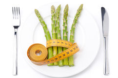 Dietetic food - asparagus wrapped with measuring tape on plate Royalty Free Stock Photography