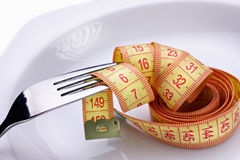 Dietetic meal. Fork and measuring tape on white plate Royalty Free Stock Photos
