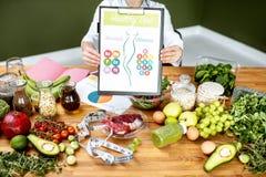 Dietetyczka z witaminy sheme przy stołem pełno zdrowi produkty fotografia royalty free
