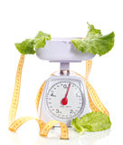 Dietic food. Green salad on weights and measuring tape isolated on white Stock Photo