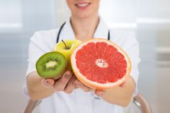 Dietician holding fresh sliced fruits Royalty Free Stock Image